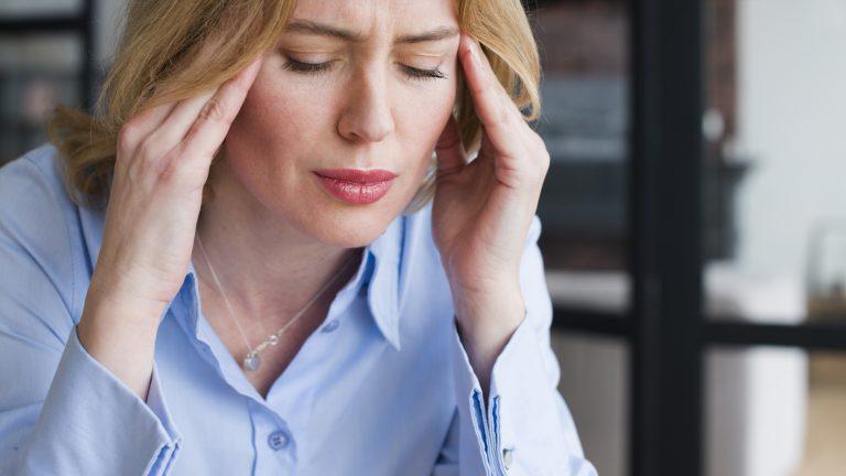 Kopfschmerzen, Stress, Frau fasst sich mit den Händen an die Schläfen